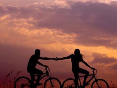 persone in bici che si tendono la mano